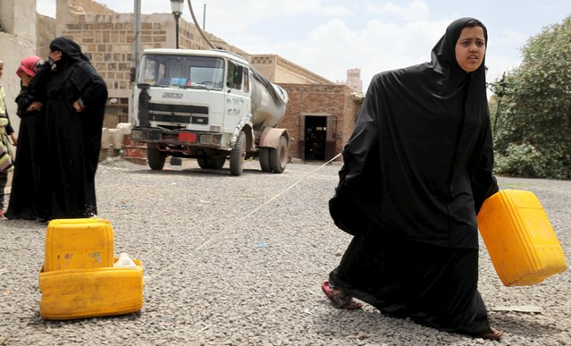 A girl holds a jerrycan filled with water from a public tap amidst water shortage in Sanaa May 13, 2015.. (Photo by Mohamed al-Sayaghi/Reuters)