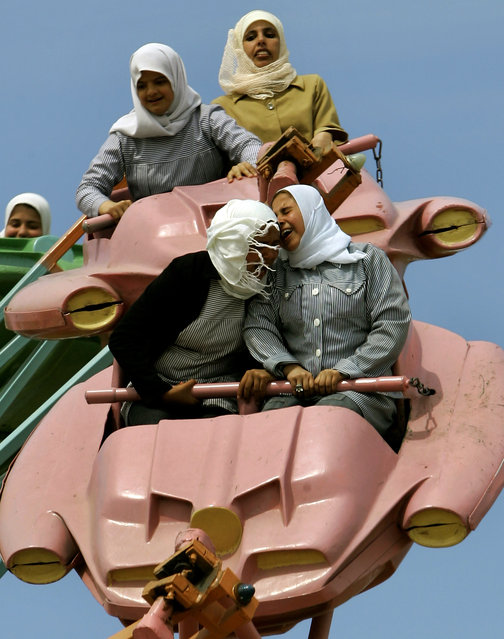 In this Sunday, March 26, 2006  file photo made by Associated Press photographer Anja Niedringhaus, Palestinians enjoy a ride at an amusement park outside Gaza City. (Photo by Anja Niedringhaus/AP Photo)