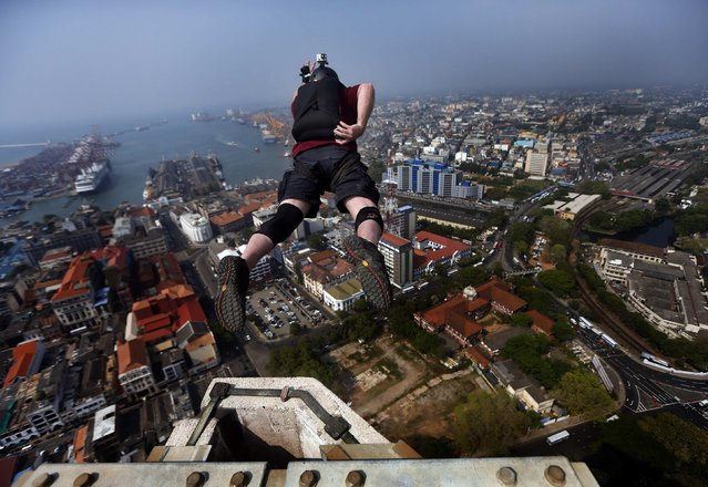 Gareth Parry, from the Canadian base jumping association, leaps off from the 40-storey World Trade Center east tower in Colombo April 3, 2014. Parry is in Sri Lanka to inspect base jump locations to organise an international competition in Colombo. (Photo by Dinuka Liyanawatte/Reuters)