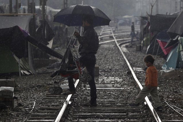 A refugee carries a baby carriage as a young boy follows under heavy rainfall at a makeshift camp for migrants and refugees at the Greek-Macedonian border near the village of Idomeni, Greece, April 24, 2016. (Photo by Alexandros Avramidis/Reuters)