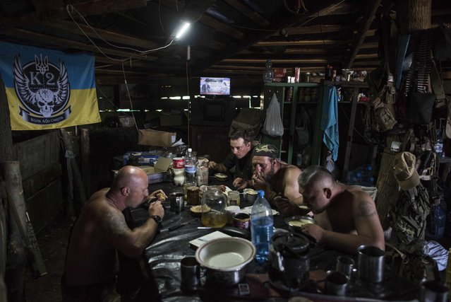 "In this photo taken Monday, June 22, 2015, Ukrainian servicemen from the Kiev-2 volunteer battalion have a meal at a frontline position in the village of Krymske, east Ukraine. The sign on a flag at left reads ""Freedom or death"". (Photo by Evgeniy Maloletka/AP Photo)"