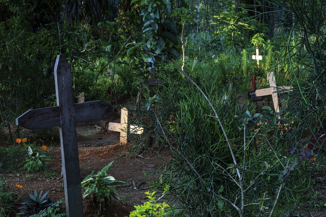 In this Tuesday, July 16, 2019 photo, sunlight shines on freshly dug graves in Beni, Congo. In a year, more than 1,600 people in eastern Congo have died of Ebola, as the virus has spread in areas too dangerous for health teams to access. (Photo by Jerome Delay/AP Photo)