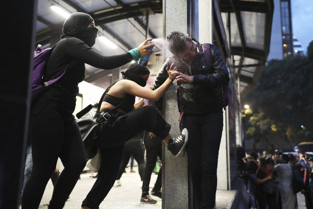 Two women assault a commuter, one spraying him in the face with paint another kicking him, at a bus station, during a protest sparked by a string of alleged sexual attacks by police officers, in Mexico City, Friday, August 16, 2019. On Friday, hundreds of women demonstrated largely peacefully in downtown Mexico City with pink spray paint and smoke. But some protesters trashed the nearby bus station. This week, an auxiliary policeman was held for trial on charges he raped a young female employee at a city museum. (Photo by Emilio Espejel/AP Photo)