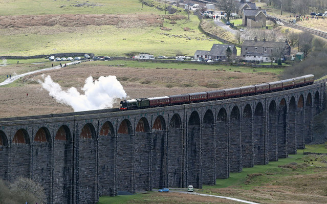 """The """"Flying Scotsman"""" crosses the Ribblehead viaduct in North Yorkshire, England as the Settle-Carlisle railway line reopens after floods on March 30, 2017. (Photo by Owen Humphreys/PA Wire)"""