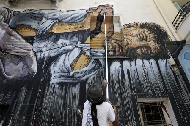 "Street artist Wild Drawing paints a mural titled ""No land for the poor"" in central Athens, Sunday, July 5, 2015. Greeks were voting Sunday in a bailout referendum that will decide the country's future, with opinion polls showing people evenly split on whether to accept creditors' proposals for more austerity in exchange for rescue loans or defiantly reject the deal. (Photo by Petros Giannakouris/AP Photo)"