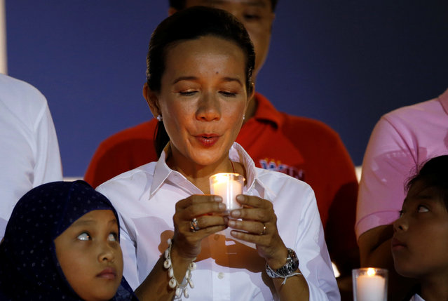 Presidential candidate Grace Poe holds a candle with other candidates and children as they pray during a final election campaign rally at Plaza Miranda, Manila in the Philippines May 7, 2016. (Photo by Erik De Castro/Reuters)