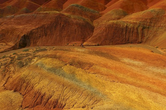 An aerial view shows a man jogging along a road inside the Danxia National Geological Park, in Zhangye, Gansu province, China, July 5, 2015. The national geological Park, covering an area of 510 square kilometres, is known for its colorful and special rock formations. (Photo by Sheng Li/Reuters)