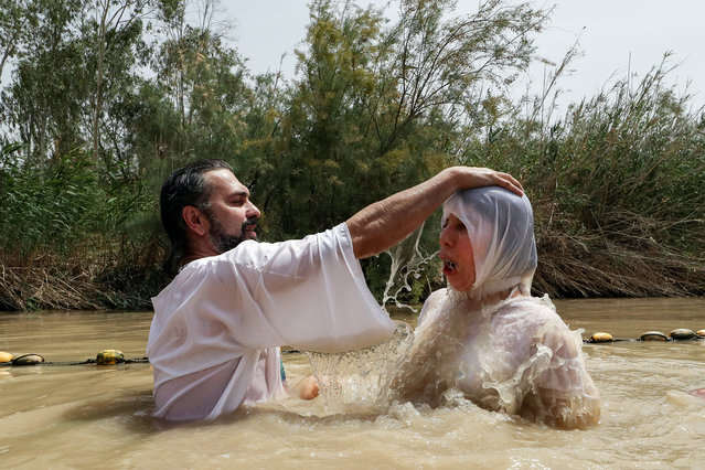 A Christian pilgrim is baptised by a priest in the muddy water of the Jordan River at the Kasser-Al-Yahud baptismal site near the West Bank city of Jericho, on April 11, 2017. According to the gospels Jesus Christ was baptised in the waters of the Jordan River by John the Baptist. (Photo by Gali Tibbon/AFP Photo)