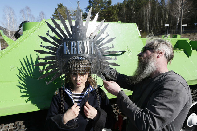 "A model waits as Russian artist Vasily Slonov (R) adjusts a work called ""Kremlin from military"" on a war monument near Russia's Siberian city of Krasnoyarsk, May 2, 2014. Slonov produced the ""Great Russia"" collection of art iron headwear styled after a Kokoshnik, the traditional Russian female headdress. Slonov is preparing to show the work in Riga. (Photo by Ilya Naymushin/Reuters)"