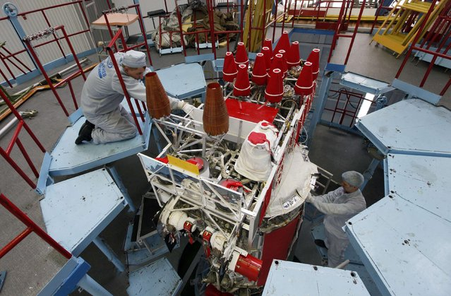 Fitters of space apparatus work on the GLONASS-M space navigation satellite inside an assembly workshop of the Reshetnev Information Satellite Systems company in the Siberian town of Zheleznogorsk, some 50 km (31 miles) northeast of Krasnoyarsk, April 2, 2014. The Global Navigation Satellite System (GLONASS) is a Russian satellite navigation system similar to the Global Positioning System (GPS) of the U.S., designed to serve for military and civil purposes. (Photo by Ilya Naymushin/Reuters)