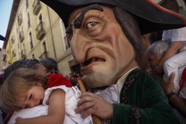 "A ""Kiliki"" or Big Head plays with a crying girl as he takes part on the daily 'Comparsa de gigantes y cabezudos' (Parade of the Giants and Big Heads) parade of the San Fermin festival in Pamplona, Spain, Thursday, July 9, 2015. (Photo by Daniel Ochoa de Olza/AP Photo)"