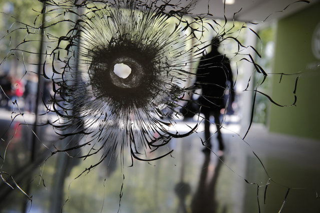 A bullet hole is pictured on a shopwindow of the Champs Elysees boulevard in Paris, Friday, April 21, 2017. France began picking itself up Friday from another deadly shooting claimed by the Islamic State group, with President Francois Hollande convening the government's security council and his would-be successors in the presidential election campaign treading carefully before voting this weekend. (Photo by Christophe Ena/AP Photo)