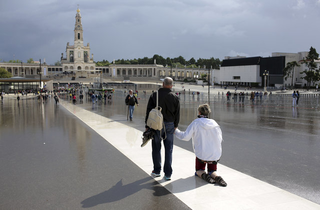 "A pilgrim walks on her knees paying penance at the Fatima sanctuary in Fatima, Portugal, Thursday, May 11, 2017. Pope Francis is visiting the Fatima shrine on May 12 and 13 to canonize two Portuguese shepherd children whose ""visions"" of the Virgin Mary 100 years ago turned the sleepy farming town of Fatima into a major Catholic pilgrimage site. (Photo by Armando Franca/AP Photo)"