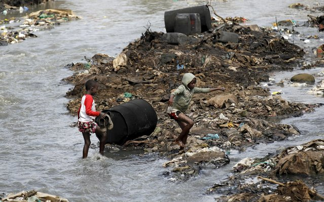 """Boys wade through the Nairobi river past empty barrels of alcohol recovered from an illegal micro-brewery for distilling traditional liquor, locally known as """"chang'aa"""", within Mathare valley slums in Kenya's capital Nairobi, July 11, 2015. According to local media, Kenyans have been advised by President Uhuru Kenyatta to refrain from destroying property where illict alcohol is found, in light of the increase in operations against illegally brewed alcohol which Kenyatta said is necessary in order for youths to be part of national development. (Photo by Thomas Mukoya/Reuters)"""
