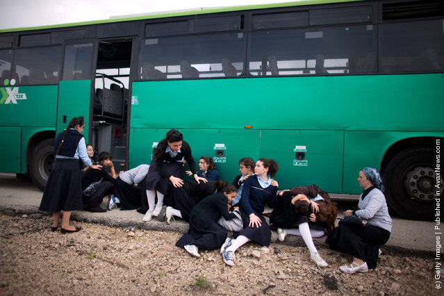 Israeli school girls take cover next to a bus during a rocket attack from the nearby Gaza Strip