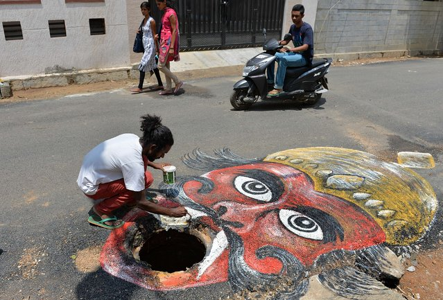 "Indian artist Badal Nanjundaswamy uses the opening of an unattended manhole in the middle of a road as a canvas to depict the Hindu God of death ""Yama"" waiting to gobble up unwary pedestrains or motorists  in Bangalore on June 6, 2014. The art installation was executed to draw the attention of the responsible municipal authorities into fixing the civic problem in an artistic way. (Photo by Manjunath Kiran/AFP Photo)"