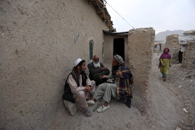 Afghan men chat outside a home on the outskirts of Kabul, Afghanistan, Sunday, April 26, 2015. (Photo by Rahmat Gul/AP Photo)
