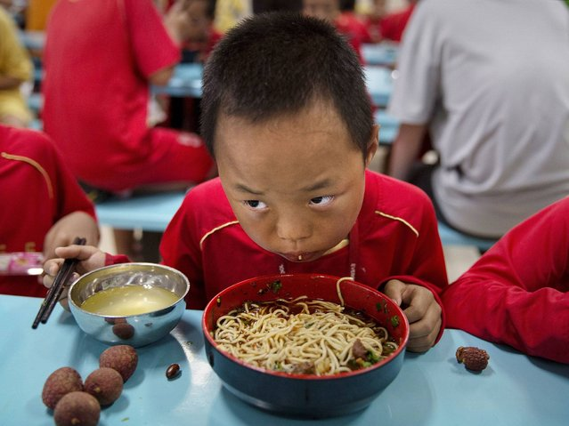 A Young Chinese football player eats his lunch on the canteen at the Evergrande International Football School near Qingyuan in Guangdong Province. (Photo by Kevin Frayer/Getty Images)