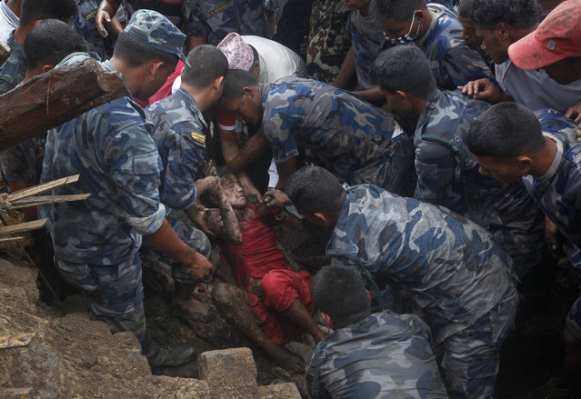 Nepalese army and police rescues team recover a dead body of a victim from the debris after a landslide in Lumle village, about 200 kilometers (125 miles) west of Kathmandu, Nepal, Thursday, July 30, 2015. Landslides in a mountain area of Nepal buried three villages Thursday, killing several people, authorities said. (Photo by Niranjan Shrestha/AP Photo)