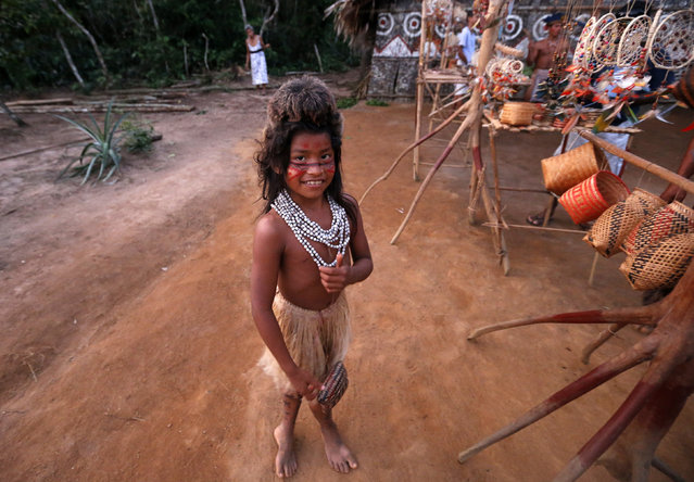 A girl of the Amazonian Tatuyo tribe poses while waiting to sell crafts to tourists in her village in the Rio Negro (Black River) near Manaus city, a World Cup host city, June 23, 2014. Because of their proximity to host city Manaus and their warm welcome, the Tatuyo have enjoyed three weeks of brisk business thanks to the World Cup. Usually, they host between 10 and 30 tourists a day. During the World Cup, this number has rocketed to 250 a day, They have become richer and other communities now come to them to sell them juices and fishes. (Photo by Andres Stapff/Reuters)
