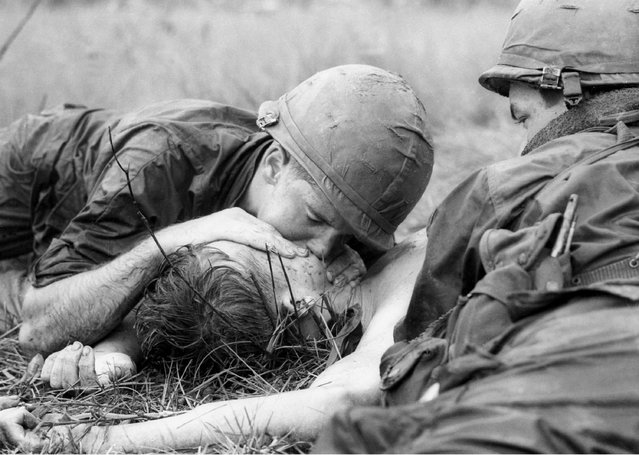 Medic James E. Callahan of Pittsfield, Mass., gives mouth-to-mouth resuscitation to a dying soldier in war zone D, about 50 miles northeast of Saigon, June 17, 1967. Thirty-one men of the 1st Infantry Division were reported killed in the guerrilla ambush, with more than 100 wounded.  (Photo by Henri Huet/AP Photo)