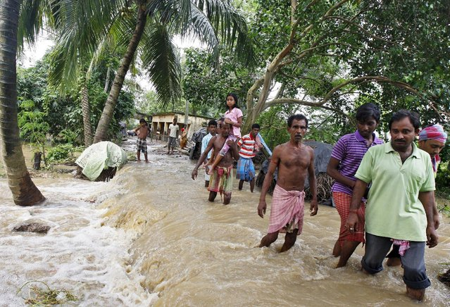 Flood-affected people wade through the flood waters at Howrah district in West Bengal, India, August 5, 2015. (Photo by Rupak De Chowdhuri/Reuters)