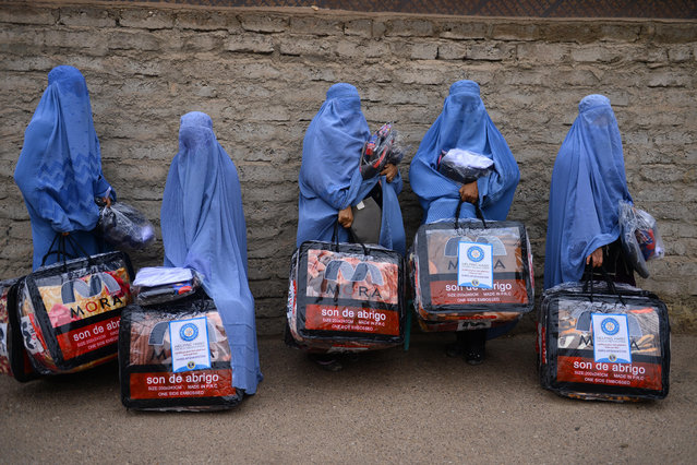 In this photograph taken on December 19, 2019, Afghan burqa-clad women stand with aid items recieved from a charity in Herat. (Photo by AFP Photo/Stringer)