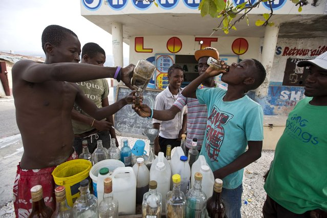Metelus Obnes pours clairin for a client as Deluson Michel, 15, drinks a small bottle of the sugar-based alcoholic drink in the Cite Soleil area of Port-au-Prince, Haiti, Tuesday, July 11, 2017. A liter of clairin sells for about $1.36, a price tag that makes all the difference in a country where about 60 percent of the population gets by on less than $2 a day. (Photo by Dieu Nalio Chery/AP Photo)