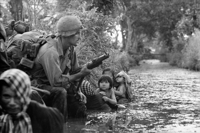 In this Jan. 1, 1966 photo, two South Vietnamese children gaze at an American paratrooper holding an M79 grenade launcher as they cling to their mothers who huddle against a canal bank for protection from Viet Cong sniper fire in the Bao Trai area, 20 miles west of Saigon, Vietnam