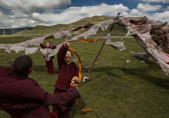 Young Buddhist novice monks play at a Tibetan nomadic summer grazing area on July 24, 2015 on the Tibetan Plateau in Yushu County, Qinghai, China. (Photo by Kevin Frayer/Getty Images)