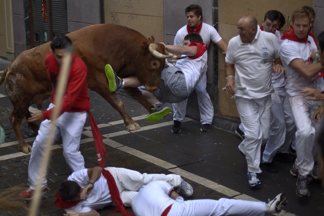 A runner is tossed by a Miura fighting bull at Estafeta corner during the eighth running of the bulls of the San Fermin festival in Pamplona July 14, 2014. A bull gored two men after breaking away from the pack and chasing them through the streets of Pamplona in the closing run of the San Fermin festival on Monday. Several men have already been gored by bulls during this year's festival but Monday's run, the eighth and last, was particularly brutal. (Photo by Vincent West/Reuters)