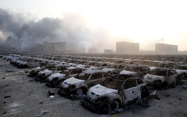Damaged cars are seen as smoke rises from the debris after the explosions at the Binhai new district in Tianjin, China, August 13, 2015. (Photo by Reuters/China Daily)