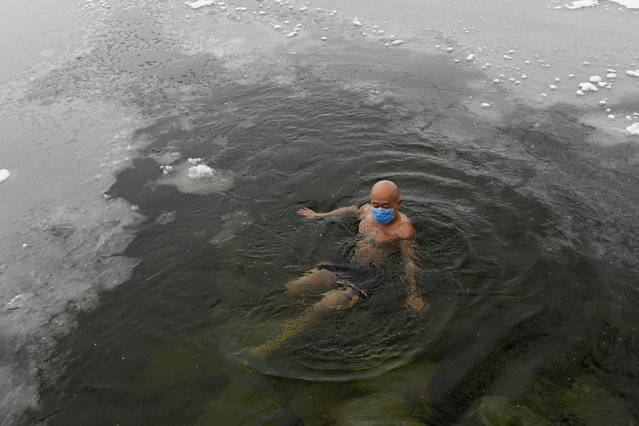 A man wearing a protective face mask swims in a partly-frozen lake as snow falls in Beijing on February 6, 2020. The number of confirmed infections in China s coronavirus outbreak has reached 28,018 nationwide with 3,694 new cases reported, the National Health Commission said on February 6. (Photo by Wang Zhao/AFP Photo)