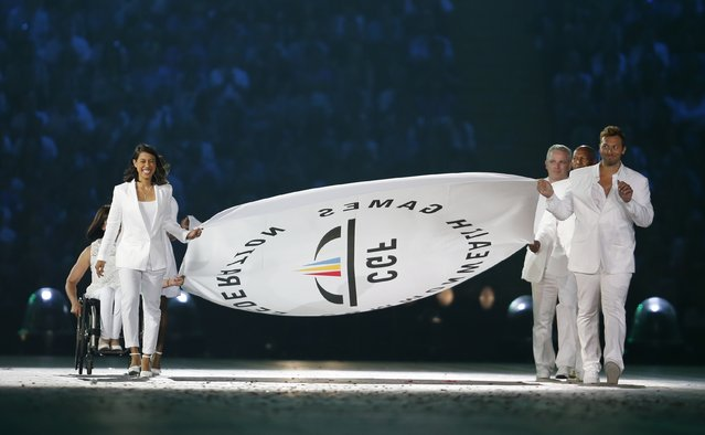 The Commonwealth Games flag is carried into the arena by former athletes including Australian swimmer Ian Thorpe, right, during the opening ceremony for the Commonwealth Games 2014 in Glasgow, Scotland, Wednesday July 23, 2014. (Photo by Frank Augstein/AP Photo)