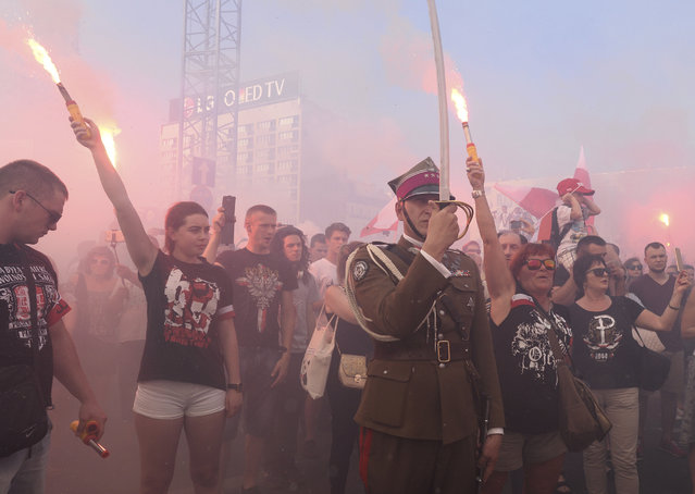 People stand on the city's main intersection holding burning flares to commemorate the 73rd anniversary of the 1944 Warsaw Uprising in Warsaw, Poland, Tuesday, August 1, 2017. Thousands of residents opened an uneven struggle on Aug. 1, 1944 in an effort to liberate the city from the Nazis and take control ahead of the advancing Soviet Red Army. (Photo by Alik Keplicz/AP Photo)