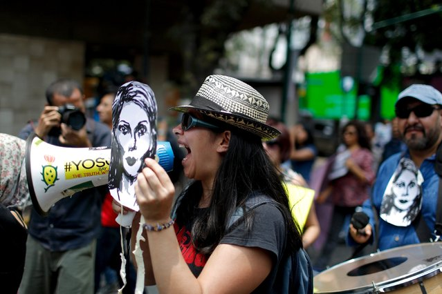 A demonstrator yells slogans as she holds a picture of Colombian citizen Mile Virginia, who was murdered along photojournalist Ruben Espinosa and three other women, during a protest in Mexico City, August 16, 2015. (Photo by Tomas Bravo/Reuters)
