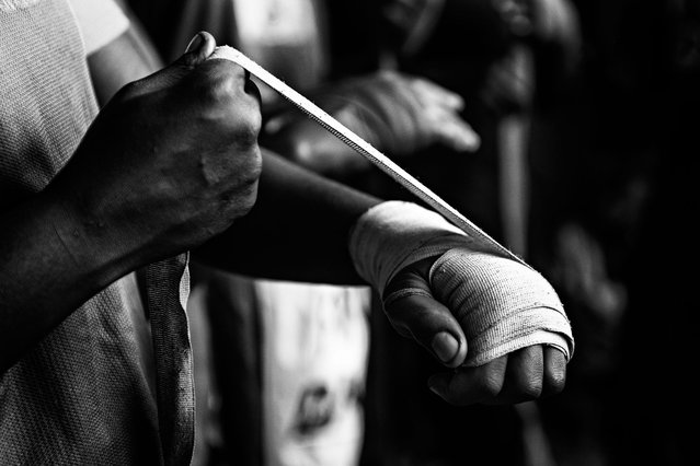 December 10, 2013 – Kampala, Uganda. With just one pair of gloves, shoes and dirty bandages, female boxers train daily for more than 2.5 hours. (Photo by Peter Bauza/ZUMA Press/VISUAL Press)