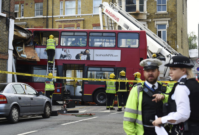 Emergency services personnel check a crashed double-decker bus in Lavender Hill, southwest London Thursday August 10, 2017. Transit officials said the bus was heading for the city's Waterloo station when it careened through the plate glass window of a kitchen shop on Thursday morning. (Photo by Lauren Hurley/PA via AP Photo)