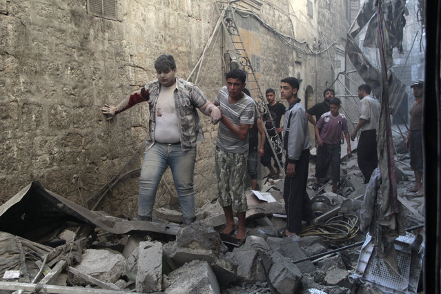 Residents help an injured man who survived what activists said were two barrel bombs dropped at a site by forces loyal to Syria's President Bashar al-Assad in Al-Shaar neighbourhood of Aleppo July 27, 2014. (Photo by Reuters)