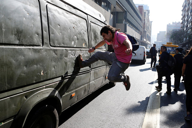 A demonstrator kicks a riot police vehicle during an unauthorized march called by the Chilean student federations to protest against government's education reform, in Santiago, Chile July 5, 2016. (Photo by Ivan Alvarado/Reuters)
