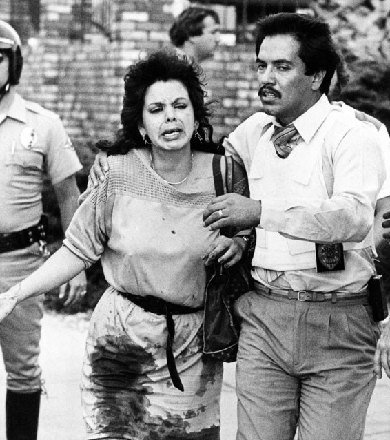 A police officer leads a bloodied woman away from the scene of a shooting rampage in a McDonald's restaurant in San Ysidro area of San Diego, Calif., July 18, 1984. On that day James Oliver Huberty shot and killed 21 people, including five children and six teens, and wounded 19, before being shot and killed by a police sniper. In the years since Huberty's rampage his gruesome death total has been surpassed, but people who study homicides say there is something lasting and shocking about the McDonald's massacre. (Photo by Lenny Ignelzi/AP Photo)