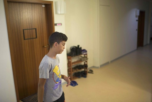 """Patriz, a migrant child from the Balkans, walks across the corridor of the  """"Sharehaus Refugio"""" community in Berlin, where Germans and migrants live together, Germany August 19, 2015. (Photo by Axel Schmidt/Reuters)"""