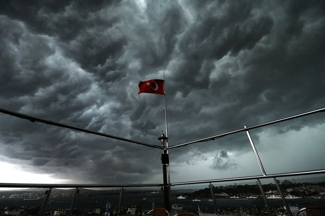 Clouds gather over the Bosphorus behind a Turkish flag during a storm on August 7, 2014, in Istanbul. (Photo by Ozan Kose/AFP Photo)