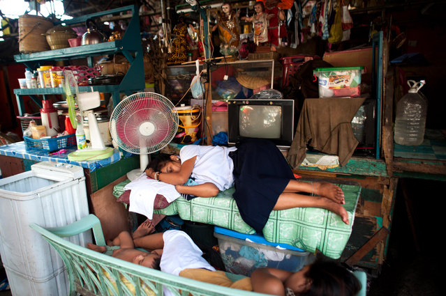 A family sleeps at a bench which also doubles as a market stall on August 11, 2014 in Manila, Philippines. (Photo by Dondi Tawatao/Getty Images)