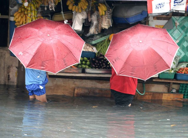 Residents wade through floodwaters after a sudden heavy downpour inundated streets in the financial district of Manila on August 12, 2015, stranding thousands of commuters and office workers. (Photo by Ted Aljibe/AFP Photo)