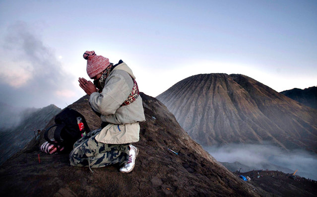 A Tengger tribesman prays at Mount Bromo during the annual Kasada ceremony in East Java on August 12, 2014. The Kasada ceremony is a festival held every 14th day of the Kasada month in the traditional Hindu lunar calender to honour Sang Hyang Widhi (God Almighty) and is based on the legend of Roro Anteng and Joko Seger from the Majapahit Kingdom, from which their Tengger tribe name originates. (Photo by Juni Kriswanto/AFP Photo)
