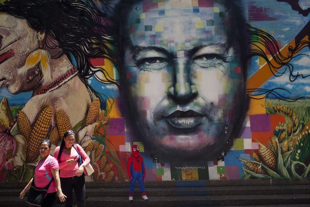 A boy dressed in a Spiderman costume poses for a photo next to a mural of Venezuela's late President Hugo Chavez painted on a wall of the Museo de Bellas Artes in Caracas, Venezuela, Tuesday, March 4, 2014. (Photo by Rodrigo Abd/AP Photo)