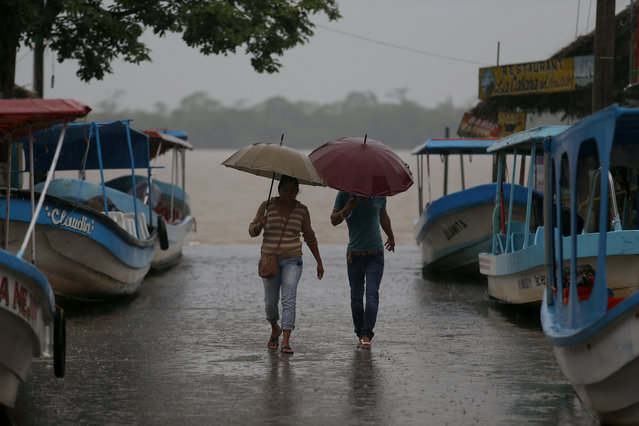 Residents walk past boats that were moved on land in preparation for the expected arrival of Hurricane Katia, in Tecolutla, Veracruz state, Mexico, Friday, September 8, 2017. Hurricane Katia in the Gulf of Mexico is stationary north-northeast of Veracruz and forecasters didn't expect much movement overnight. (Photo by Eduardo Verdugo/AP Photo)