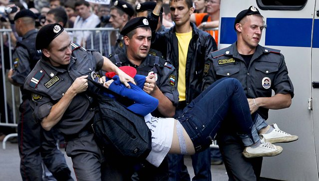 Police officers detain a supporter p*ssy Riot outside the court  in Moscow. (Photo by Alexander Zemlianichenko/Associated Press)
