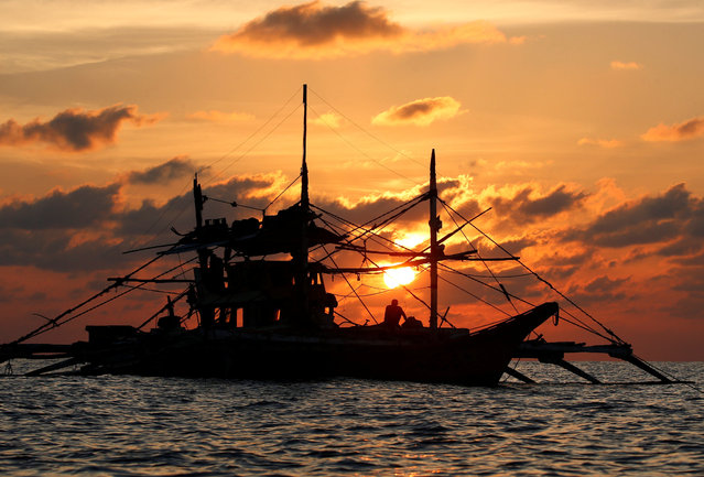 A Philippine boat fishes during sunset at the disputed Scarborough Shoal on April 5, 2017. (Photo by Erik De Castro/Reuters)